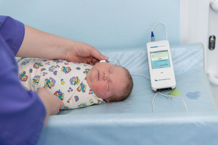 Врач проверяет новорожденного аудиометром