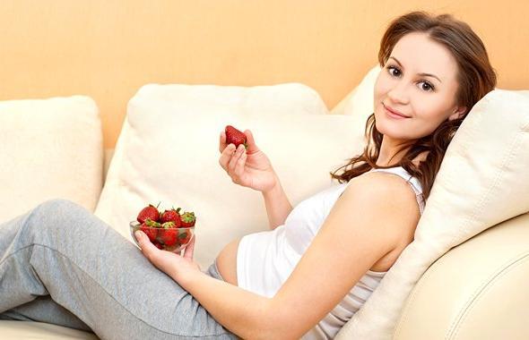 Беременная девушка с миской ягод