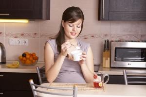 Беременная девушка ест йогурт